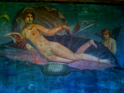 The Goddess of Love.  Is one of my favorite frescoes inside the many houses of Pompeii.  This fresco was discovered in 1952 located on the back wall of the garden, it portrays Venus with 2 cherubs in a pink seashell.