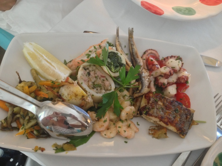 Another reach plate of fresh seafood including marinated anchovies, fresh Gulf shrimp, octopus,  stuffed squids, grilled fish and langostinos