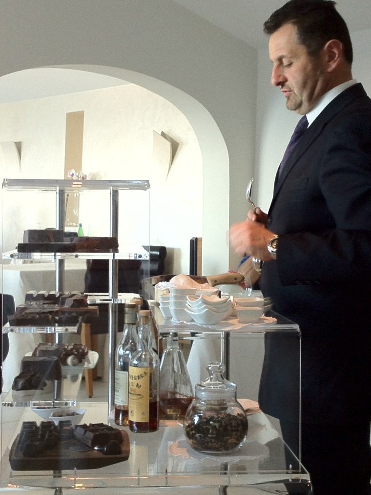 The maître offering a selection of the finest Italian, Belgium and Swiss blocks of chocolates with choice of aged rum, Armagnac, cognacs and other selected digestives.